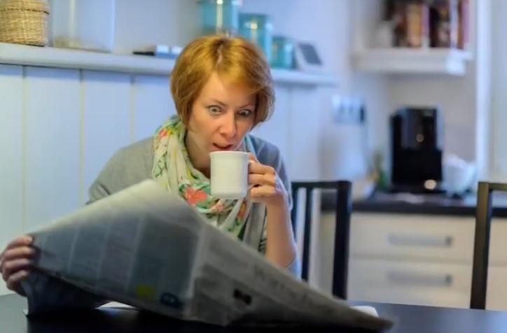 写真で一言「新聞を見て驚く女性」